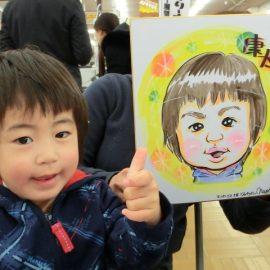 デフォルメタッチの似顔絵と一緒に笑顔で写真を撮る男の子
