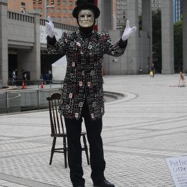 お面を被ってパントマイムやアニメーションダンスをする大道芸人