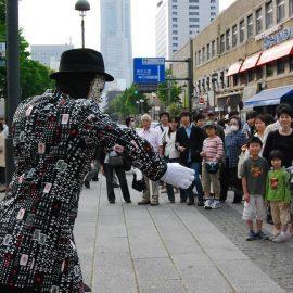 たくさんの人に囲まれてアニメーションダンスをするパントマイムパフォーマー