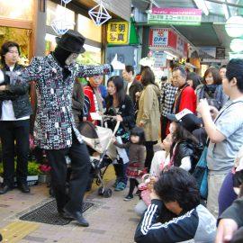 商店街でパントマイムショーをして注目を浴びる大道芸人