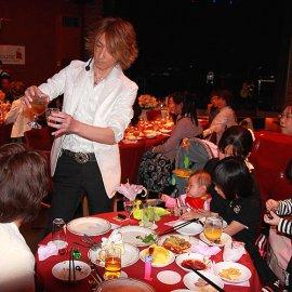 パーティーで各テーブルを回って目の前でマジックを披露するマジシャン