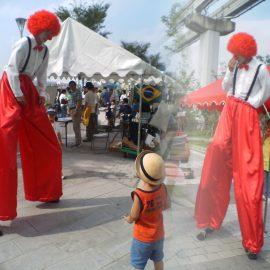 巨大ピエロに扮して小さな子どもを楽しませるスティルトパフォーマー
