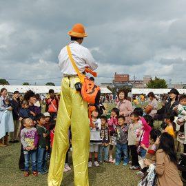 イベントで子ども達に囲まれるハロウィンの衣装のスティルトパフォーマー