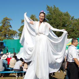 白い衣装で会場内を練り歩くスティルトパフォーマー