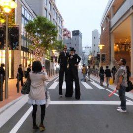路上で写真撮影に応じるスティルトパフォーマー