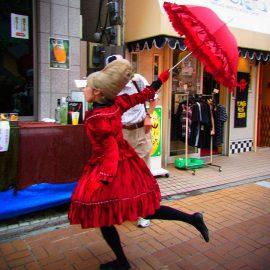 一際目立つ赤い衣装を着て路上パフォーマンスをするパントマイムアーティスト