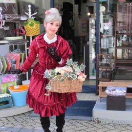 お店の前でパントマイムをして道行く人の目を引く女性パフォーマー