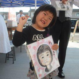 女性似顔絵師が描いた似顔絵を嬉しそうに持っている女の子