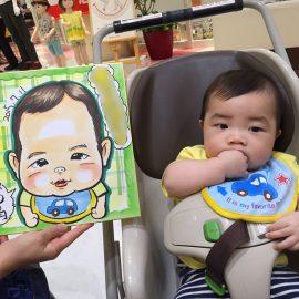 ショッピングセンターの一角で似顔絵師が描いた赤ちゃんの似顔絵