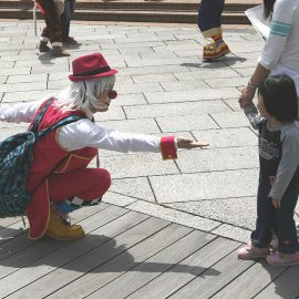 路上で通行人に対してパフォーマンスをする男性クラウン(ピエロ)