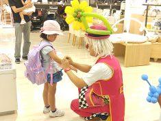 女の子に花のバルーンをプレゼントするピエロ(クラウン)