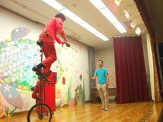 一輪車に乗って剣を使ったジャグリングをする大道芸人