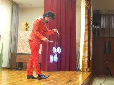 光るコマ(ディアボロ)でのジャグリングをする大道芸人