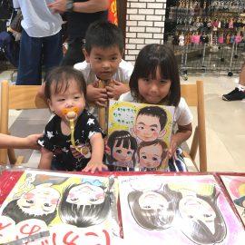 ショッピングセンターの一角で女性似顔絵師が描いた兄弟の似顔絵