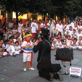 海外でバルーンアートショーをして子供に囲まれる女性パフォーマー