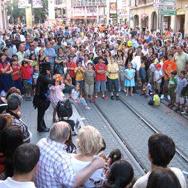 外国で多数の観客を前に路上パフォーマンスをする女性バルーンパフォーマー
