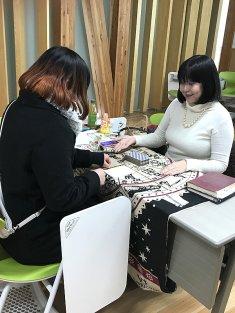 文化祭の無料タロット占いコーナーで女性を占っている占い師