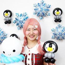 可愛らしい雪だるまとペンギンのバルーンアートを持っている女性バルーンパフォーマー