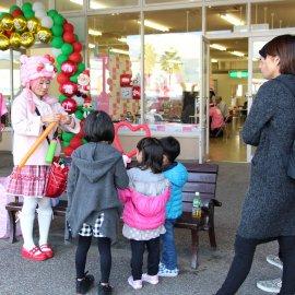 ピンクの可愛い衣装を着て子ども達にバルーンアートを作ってあげる女性バルーンパフォーマー
