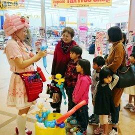 ショッピングセンターを練り歩きながらお子様にバルーンをプレゼントする女性バルーンアーティスト