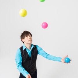 ジャグリングボールを披露する男性の大道芸人