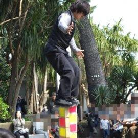 たくさんの観客の前でローラーバランスを披露する山口県出身の大道芸人