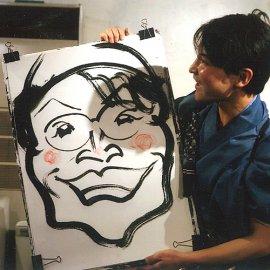 大きな紙に墨で女性の似顔絵を描いた男性似顔絵パフォーマー