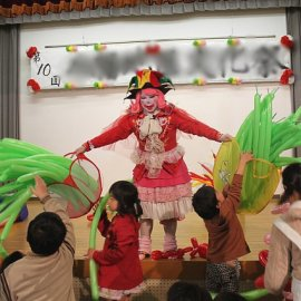 地域の祭りでお子様向けにバルーンアート教室をするバルーンパフォーマー