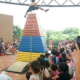 観客の目の前で巨大跳び箱に挑戦するアクロバットパフォーマー
