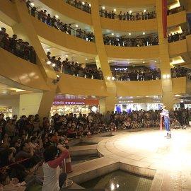 大勢の観客に囲まれながら独自のパフォーマンスショーを展開する大道芸人