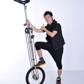 高さ2mもある一輪車の上でジャグリングなどのパフォーマンスをする大道芸人