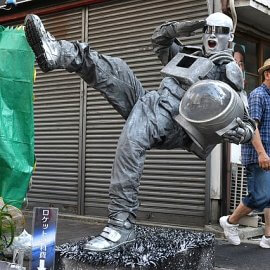 片足が浮いた状態で止まるという彫像パフォーマンスを街中で行うスタチューパフォーマー