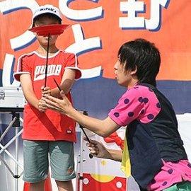 ステージ上で男の子に皿回しを教える男性パフォーマー