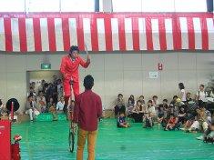 一輪車に乗りながら剣でジャグリングをする大道芸人