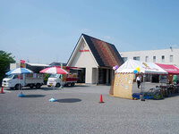 住宅展示場の駐車場に配置された食品移動販売車やテントの様子