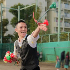 屋外イベントにてバルーンアートを披露するパフォーマー