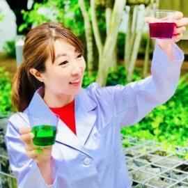 カラフルな液体を両手に持って科学実験パフォーマンスを披露する女性の科学実験パフォーマー